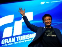 Gran Turismo creator Kazunori Yamauchi of Japan waves to the crowd during the International presentation of the new Sony PlayStation