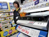 A shop assistant stands near DVD players on display at an appliance store in Tokyo.