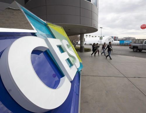 People pass a CES sign during preparations for the 2016 International CES trade show at the Las Vegas