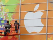 Workers apply the Apple logo to the exterior of the Yerba Buena Center for the Arts in preparation for an Apple special event Jan. 26, 2010 in San Francisco, California.