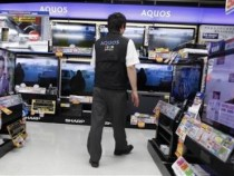 A salesperson walks among Sharp Corp's Aquos liquid-crystal display (LCD) televisions displayed at an electronic store in Tokyo in this June 8, 2012 file photograph.