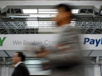 Visitors walk past an Ebay and PayPal banner at the Mobile World Congress in Barcelona February 28, 2012.