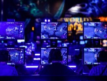 Visitors try out the massively multiplayer online role-playing game 'World Of Warcraft' at the Blizzard Entertainment stand at the Gamescom 2015.