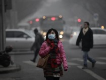 A woman wears a mask to protect herself from air pollution in Beijing, China