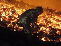 French Charles Riviere catches a piece of lava, on
