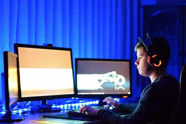 Man gaming with three monitors