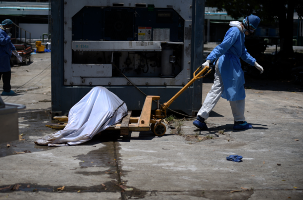 Health workers wearing protective gear bring a dead body past a refrigerated container outside of Teodoro Maldonado Carbo Hospital amid the spread of the coronavirus disease (COVID-19), in Guayaquil