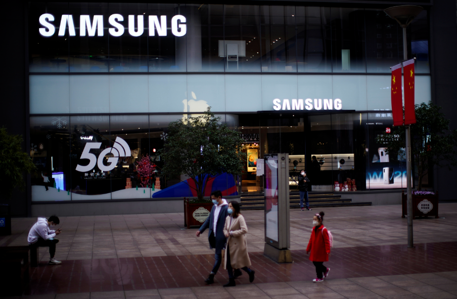 FILE PHOTO: People wears masks in front a Samsung Store at a main shopping area, in downtown Shanghai