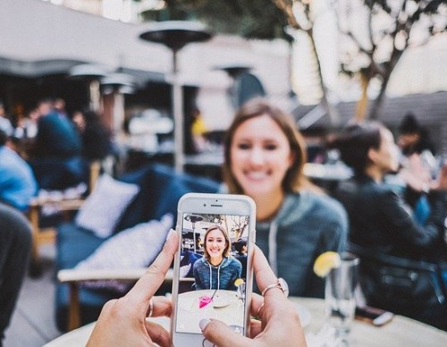 iPhone being used to take a photo of a woman