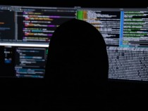 Suspicious man in front of computer screen
