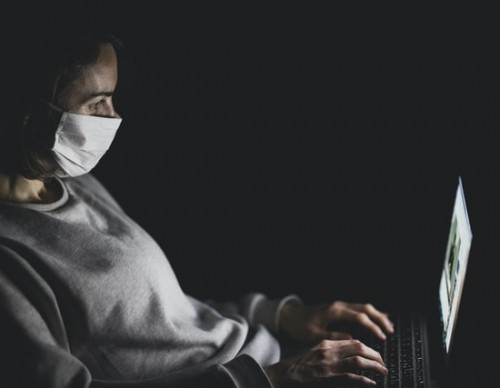 Person with mask using MacBook