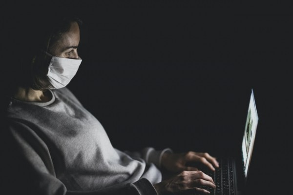 Woman with mask using MacBook