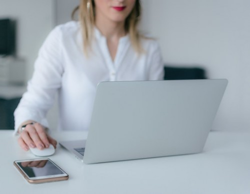 Woman using laptop with wireless mouse