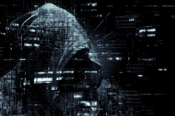 Hacker with a hood and code in front of him
