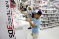 Boys try out Nintendo's 3DS game software at an electronic store in Tokyo July 25, 2012.