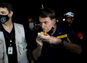 The moment when unmasked Brazil President Jair Bolsonaro was jeered at as he ate a hotdog and posed for a picture with a young girl last Saturday, May 23, was caught on cam.