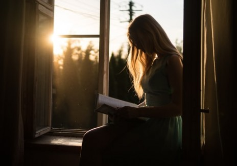 Woman reading book while sitting on windowsill