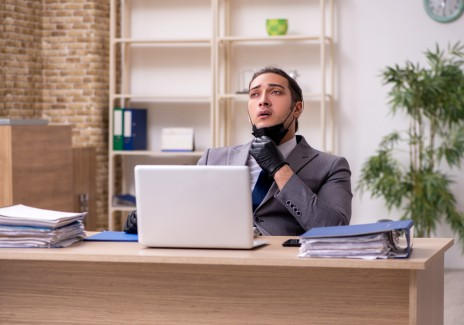 Young male employee in the office during pandemic disease
